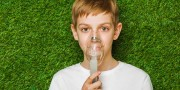 Portrait of a boy breathing through inhaler mask over spring green grass background