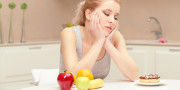 It is hard to make a choice. Young woman sitting at her table in the kitchen and trying to choose eating either banana, apple and orange or sweet donut