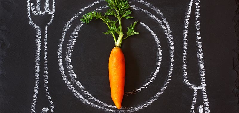 Healthy food concept. Fresh organic carrot on a chalk painted plate.