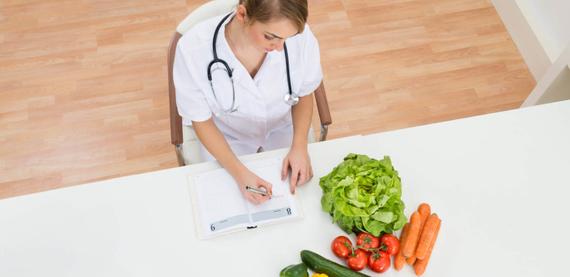 High Angle View Of Female Dietician Writing Prescription With Vegetables On Desk