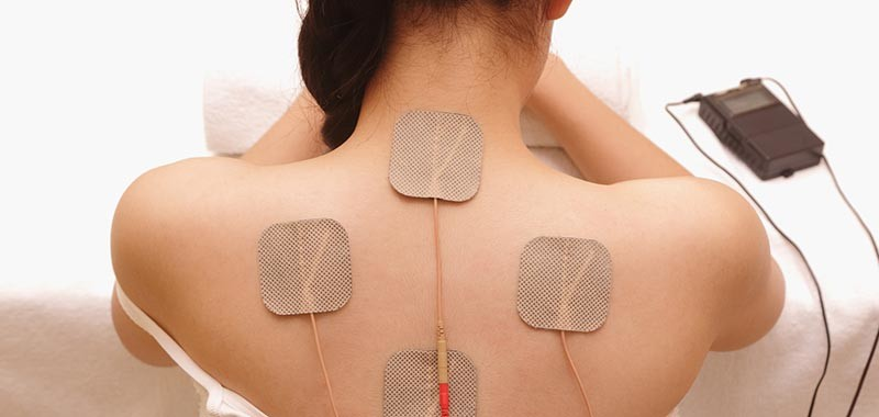 Asian woman is doing massage of electrical -stimulation ( TENs ) for the back