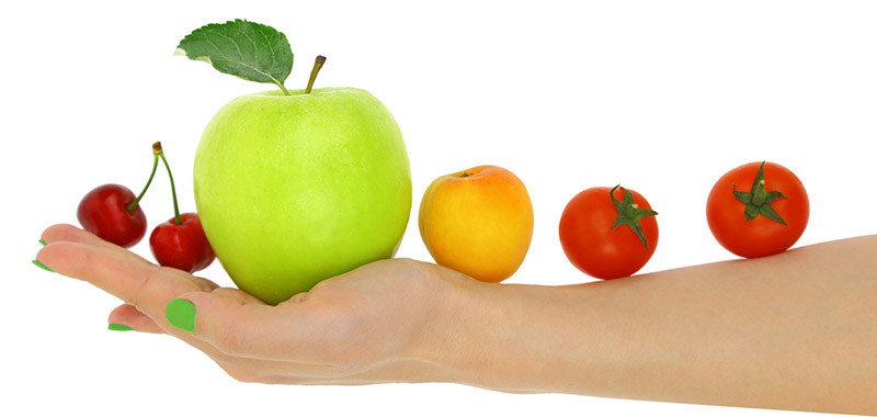 Female hand with a row of fresh colorful fruits